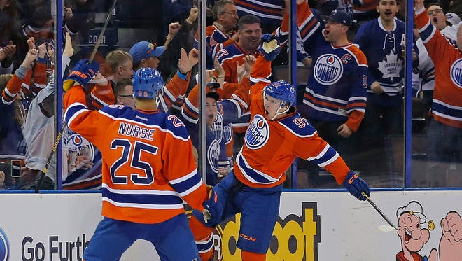 Edmonton Oilers forward Connor McDavid (97) celebrates his first period goal against the Toronto Maple Leafs with defensemen Darnell Nurse (25) at Rexall Place.