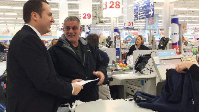 Zack Bossick, director of the Grand Ledge Meijer store, gives Jeff Penfield a letter. Penfield's shopping trip was free as part of the Very Merry Meijer effort Dec. 10, 2016.