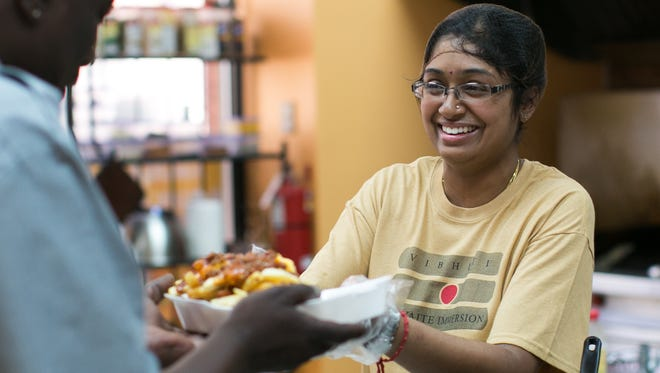 Anita Kumaran serves lunch at Amudam Café in downtown Rochester on Friday, May 8, 2015. The new restaurant is located near the RTS Transit Center on North Clinton Avenue downtown.