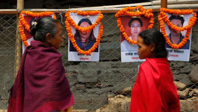 Nepalese women look at portraits of victims of a 2015 earthquake during an event to mark the third anniversary of the earthquake in Katmandu, Nepal, on April 25, 2018.