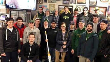 Payton Walters, 16, of Kendall (front center, holding stick) surrounded by members of the College at Brockport hockey team and Jimmy Zisovski (center, holding white stick), owner of Jimmy Z's. A fundraiser for Payton will be held at Jimmy Z's on Feb.13.