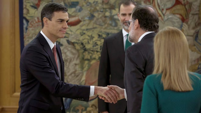 Spain's socialist leader Pedro Sanchez (left) shakes hands with former Prime Minister Mariano Rajoy (right) in the presence of Spain's King Felipe VI after being sworn in at a ceremony at the Zarzuela Palace on the outskirts of Madrid, Spain,