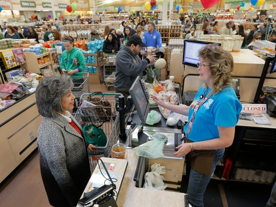 Sprouts head cashier Merry Robitaille checks out Martha