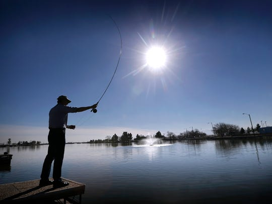A man fishes at Ascarate Lake, in El Paso, Texas, Thursday,
