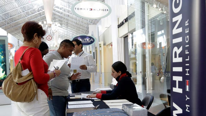 A Tommy Hilfiger employee talks with job applicants during a job fair at Dolphin Mall, in Miami.
