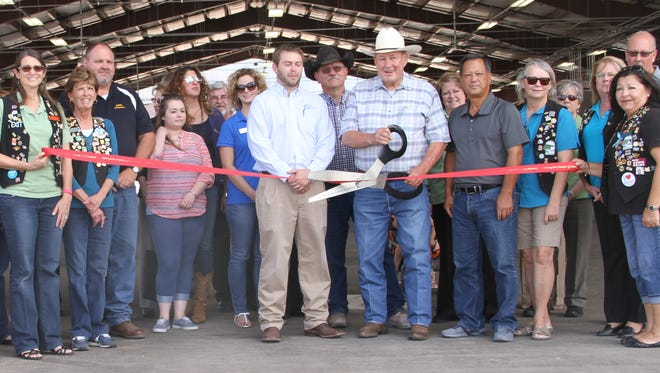 The Otero County Fair Board members and Alamogordo Chamber of Commerce members cut the ribbon to open the new Otero County Fair & Rodeo pavilion two weeks ahead of the Fair's first day Aug. 24. Fair Board member Reid Griggs stands next to Fair Board Chairman Bill Mershon prior to Mershon officially cutting the ribbon and officially opening the $1.2 million pavilion replaces the Frontier Village. The facility is about 24,000 square feet and can accommodate up to 70 vendors. The Otero County Fair & Rodeo is between Aug. 24 and Aug. 27.