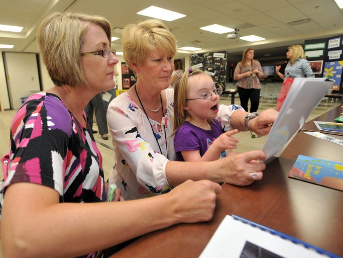 Teacher Cathy Wilkinson reads with kindergarten student Anna Skomp, and her mom Deborah, left, at a display documenting the Hinkle Creek Elementary School life skills class project to grow pansies and marigolds from seed, at an open house to highlight the life skills achievements for children with special needs, at the Noblesville Schools Educational Services Center Monday June 2, 2014. The students grew the plants from seed, then planted them at the Agape program facility where many life skills students participated in horsemanship.