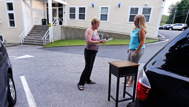 """Susan Locke, left, counts out her cash as she purchases a table  from Michele Velleman in the """"online safe zone"""" outside the police station in Georgetown, Mass., in 2015. Around the nation, in police department parking lots festooned with surveillance cameras, authorities are setting up an """"online safe zones"""" where people meeting via Craigslist or buying goods via eBay can encounter each other without fear of assault or abduction. A new app has a list of such places. With a click using your cellphone's geo-location feature, you can find them on a map."""