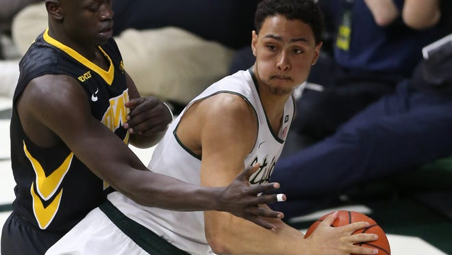 Michigan State's Bryn Forbes passes against Iowa's Peter Jok during the second half of MSU's 76-59 loss Thursday at the Breslin Center.