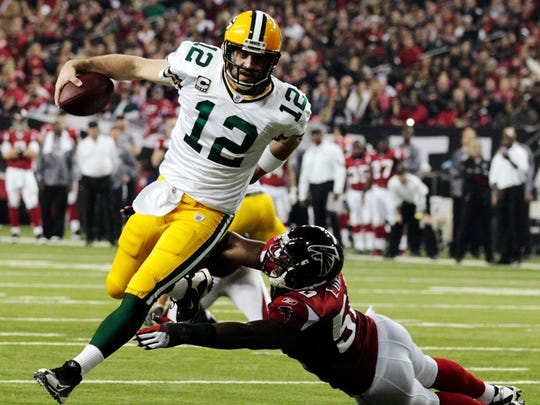 In this Jan. 15, 2011, file photo, Green Bay Packers quarterback Aaron Rodgers  scrambles past Atlanta Falcons linebacker Curtis Lofton on a 7-yard touchdown run during the second half of an NFL divisional playoff football game in Atlanta.