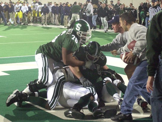 Teammates and fans mob TJ Duckett after he caught the game-winning touchdown to beat Michigan 26 to 24 in 2001.
