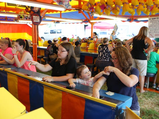 "At right, Jessica Cuff, of Ulster Park, with her daughters Abigail, 11, and Emma, 2, play ""I Got It"" at the Ulster County Fair on Tuesday. Jessica Cuff has been coming to the fair since she was a child, and passes the tradition on to her daughters ."
