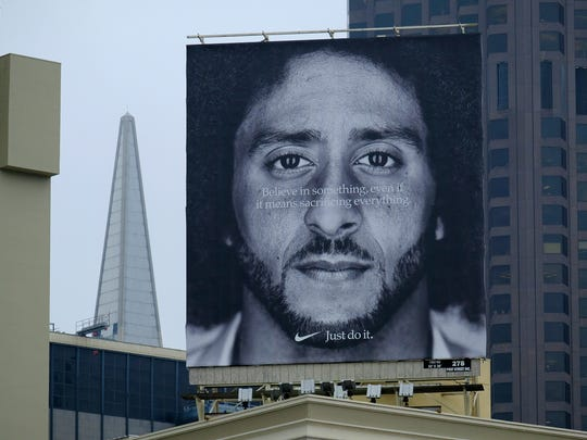 FILE - In this Sept. 5, 2018, file photo, a large billboard stands on top of a Nike store showing former San Francisco 49ers quarterback Colin Kaepernick, at Union Square in San Francisco. Colin Kaepernick and Eric Reid have reached settlements on their collusion lawsuits against the NFL, the league said Friday, Feb. 19, 2019.  (AP Photo/Eric Risberg, File)