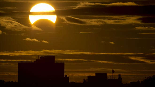 A partial solar eclipse is seen just after sunrise over Queens, N.Y., on Nov. 3, 2013.