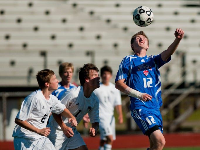 St. Clair senior Scott Bradley heads the ball in front of a group of Marine City players during a soccer game August 27, 2014 at East China Stadium.