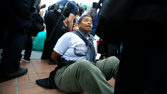 San Diego police officers in full riot gear arrest an anti-Trump demonstrator.