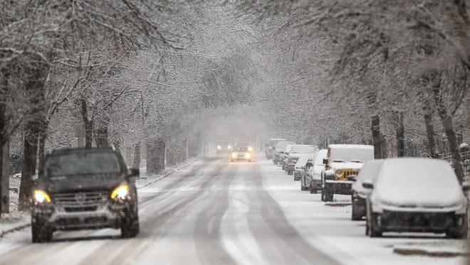 Drivers travels through heavy snow toward downtown Indianapolis on North Pennsylvania Street, Tuesday, Dec. 13, 2016.