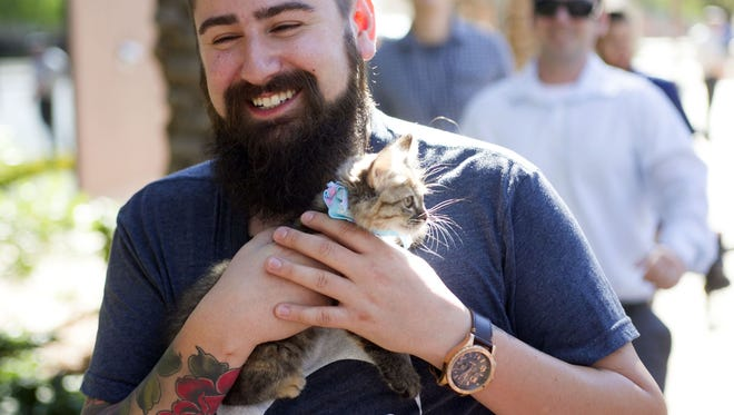 """Gabe Williams a senior marketing manager with Uber holds the kitten """"Simba"""" outside the 12 News studios in Phoenix on Wednesday, October 29, 2014. The ride sharing comparing Uber has a cross promotion with the Arizona Humane Society where people can donate $30 or more to the Arizona Humane Society for 15 minutes of cuddling time with a kitten and the option to adopt. Uber will drive the kittens out to interested people."""