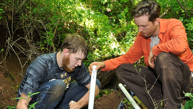 J.P. Gannon, right, WCU assistant professor of geology, and junior geology major Joshua Tatum install a groundwater well at the Western Carolina Hydrologic Research Station on WCU's campus as a part of their summer research project on groundwater chemistry.