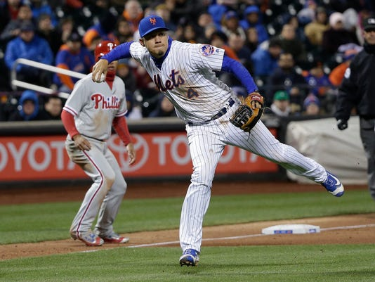 New York Mets third baseman Wilmer Flores (4) makes an off-balance throw on a slow roller hit by Philadelphia Phillies' Maikel Franco during the ninth inning of a baseball game, Saturday, April 9, 2016, in New York. Franco was safe at first on the play. (AP Photo/Julie Jacobson)