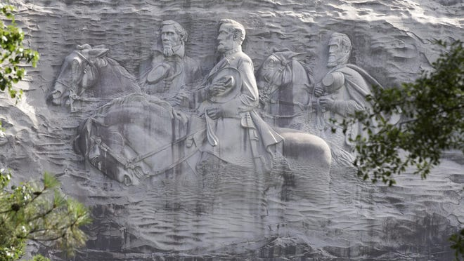 Georgia officials are trying to decide what, if anything, to do about a huge sculpture that memorializes three of the South's Civil War heroes but causes offense to blacks and others.
