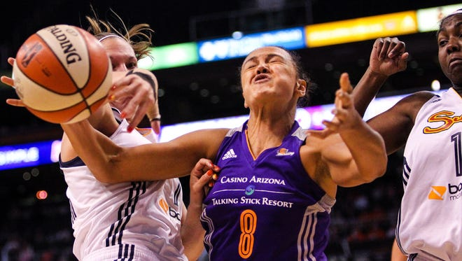 The Mercury's Mistie Bass is hit as she goes up for a shot between Sun defenders at US Airways Center in Phoenix on Friday, June 19, 2015.