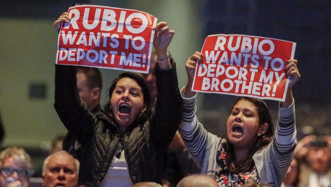 A pair of immigration protesters yell and hold signs targeting Marco Rubio.