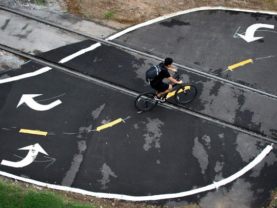 A cyclist rides through a bike path intersection with