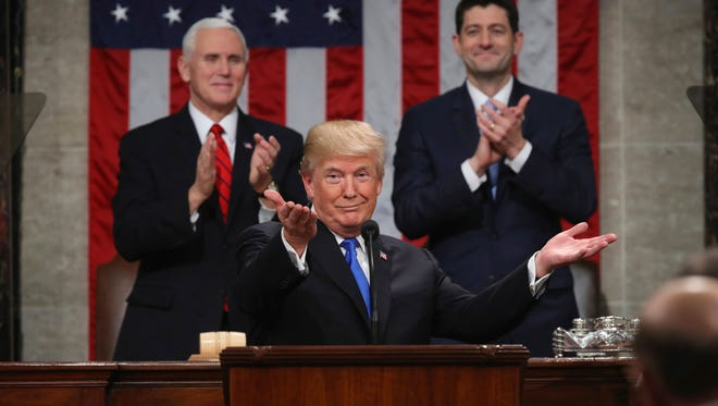 President Donald Trump gestures as delivers his first State of the Union address in the House chamber of the U.S. Capitol to a joint session of Congress on Tuesday in Washington, as Vice President Mike Pence and House Speaker Paul Ryan applaud.