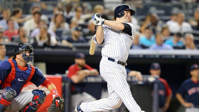 Yankees catcher Brian McCann hits a two-run home run against the Boston Red Sox during the eighth inning on Friday in New York.