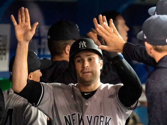 New York Yankees' Neil Walker is met by teammates in the dugout after scoring in the sixth inning of a baseball game against the Toronto Blue Jays in Toronto, Friday, March 30, 2018. (Fred Thornhill/The Canadian Press via AP)
