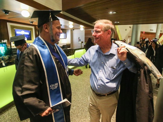 Cal State San Bernardino Palm Desert Campus' Class of 2017 graduate Edgar Rivera, left, of Indio, is greeted by his adviser during his commencement ceremony on Thursday, June 14, 2017 at The Show in Rancho Mirage. Rivera became addicted to drugs at the age of 16 and has been sober for 10 years. Rivera plans to become a therapist.