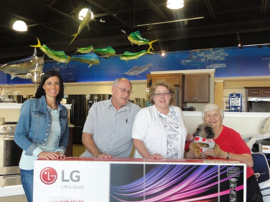 Amy Thofner, niece of Jetson's owner, John Jetson, presents the LG TV donated by Jetson's to Dogs & Cats Forever raffle winners Mr. and Mrs. Knechtges. Jay Apicella (right).chairman of Dogs & Cats Forever is holding her newly adopted friend.