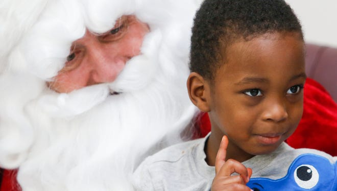 Jimmie McDonald, 3, of Newark, hangs out with Santa during the Delaware National Guard annual children's party at the Guard's Newport Gap Pike facility Saturday.