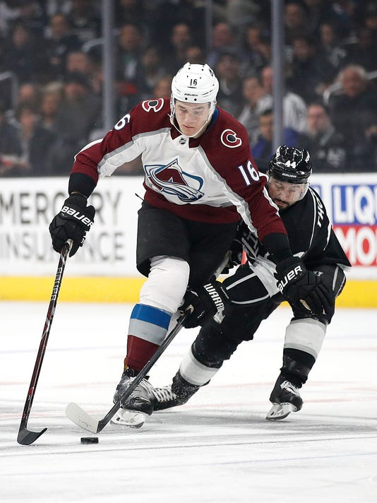 Colorado Avalanche's Nikita Zadorov, left, of Russia, moves the puck under defense by Los Angeles Kings' Nate Thompson during the first period of an NHL hockey game Monday, April 2, 2018, in Los Angeles. (AP Photo/Jae C. Hong)
