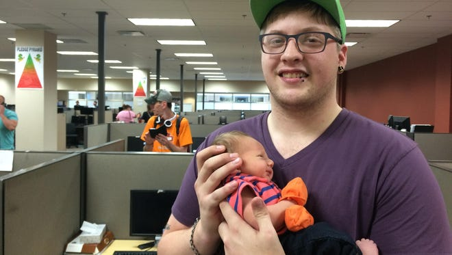 Andrew House cradles his newborn son, Quinton, inside Strategic Fundraising's Oshkosh office Tuesday. Strategic closed Monday, and laid off House along with more than 150 other workers.