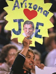 A fan in the stands at the Fiesta Bowl holds up a sign