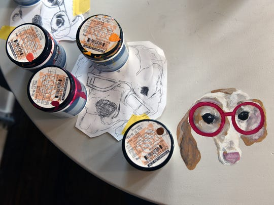 Paintings of dogs wearing glasses adorn a table at The Painted Cottage in New Concord. Co-owner Missy McDonald purchases furniture from auctions and Craiglist to repaint and sell in her store along with seasonal crafts and home decor.