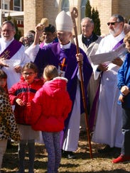 Surrounded by children, Bishop Robert Morneau prepares