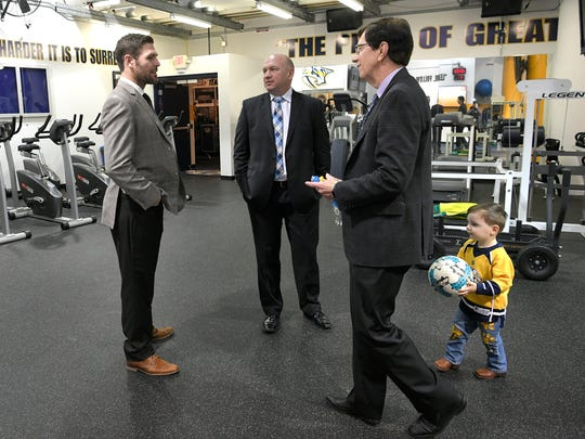 Predators center Mike Fisher, Professional Scout Rob Cowie adn General Manager David Poile talk before the game while Polie's grandson, Wyatt, plays with a soccer ball before a game at Bridgestone Arena on Feb. 25, 2018.