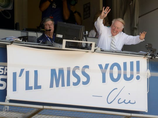 Vin Scully waves to the fans from the broadcast booth before his final game at Dodger Stadium, between the Los Angeles Dodgers and the Colorado Rockies, on Sept. 25, 2016.