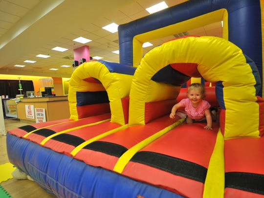 Two-year-old Kynslei Dahlquist of Wausau crawls out of a bouncy house in July at the newly installed Jump On It play area in the Wausau Center mall.