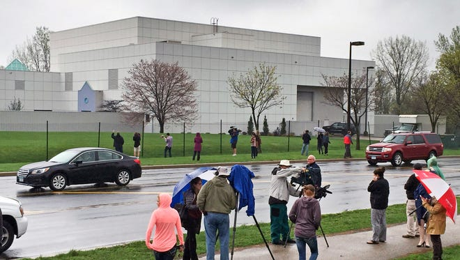 FILE - In this April 21, 2016 file photo, people stand outside the entertainer Prince's Paisley Park compound in Chanhassen, Minn. Following a Chanhassen City Council rezoning vote on Monday, Oct. 24, 2016, Prince's Paisley Park recording studio and home will begin operating as a permanent museum. The museum's website said tours will begin again Friday, Oct. 28.