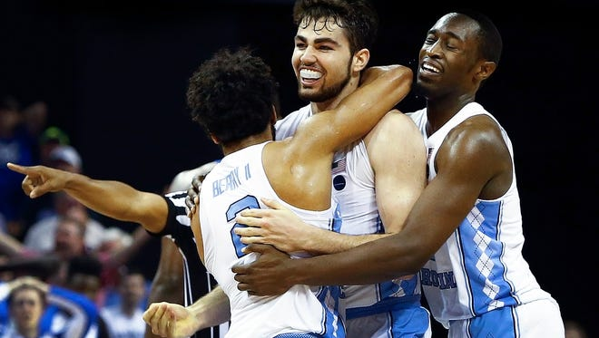 University of North Carolina forward Luke Maye  (middle) celebrates with teammates Joel Berry II (left) and Theo Pinson (right) after hitting a game winning shot with .3 seconds on the clock to defeat University of Kentucky 75-73 to advance to next weeks NCAA tournament Final Four.