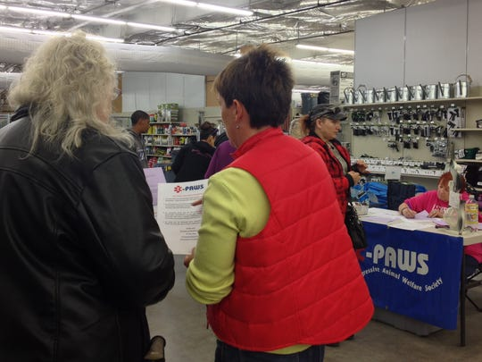 A volunteer with the C-PAWS organization goes over requirements to receive assistance from the Pet Food Assistance Program with a guest Saturday morning at the Carlsbad Tractor Supply