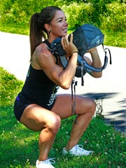 Marcela Perea, owner and coach at CrossFit 100, demonstrates the front squat using a weighted backpack.