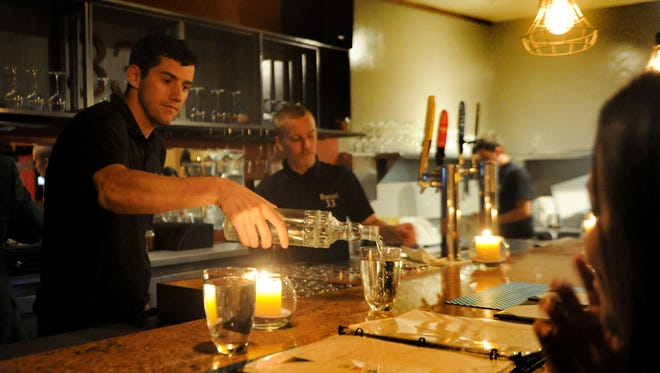 Dan D'Addeo serves his customers at Barrel 33 in Ventura. The restaurant focuses on wines, beer and coffee, etc. They also make a Ventura pizza, which features goat cheese and tomatoes on an almost sheer base. The low light with candles set the low light mood.