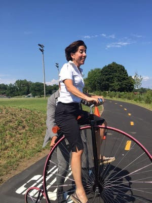 Gov. Gina Raimondo rides an old-fashioned high-wheeled bicycle during an event to mark the opening of a new section of the Blackstone River Bikeway, in 2017.