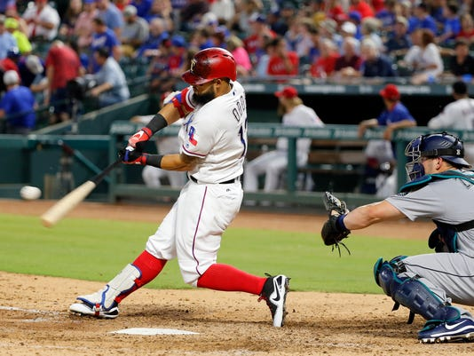 Texas Rangers' Rougned Odor hits a two-run home run as Seattle Mariners' Mike Zunino watches during the fourth inning of a baseball game, Tuesday, Aug. 1, 2017, in Arlington, Texas. (AP Photo/Tony Gutierrez)