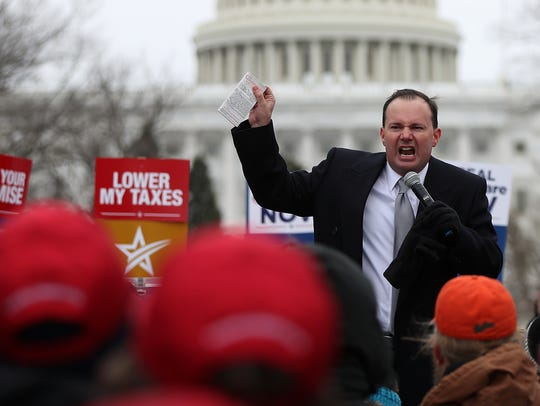 Sen. Mike Lee, R-Utah, holds up a copy of the U.S.